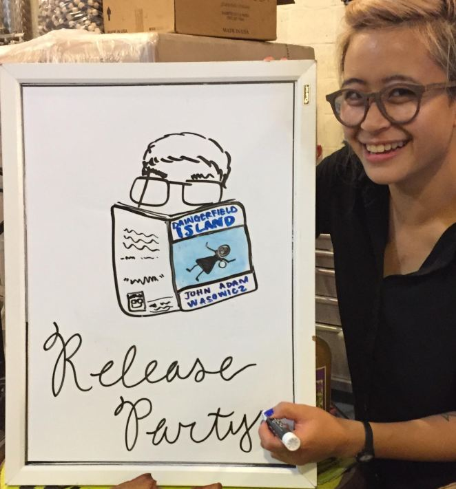 Artist Michelle Tran presents a whiteboard with her illustration of a person reading DAINGERFIELD ISLAND.