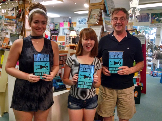 Author John Adam Wasowicz and two Island Bookstore employees stand in an independent bookstore, holding up copies of DAINGERFIELD ISLAND.